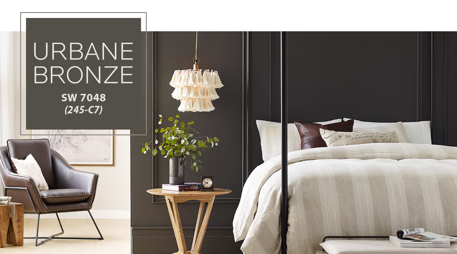 Sherwin Williams Urbane Bronze 2021 Color of the Year.  Image with Urbane Bronze accent wall behind a neutral striped bed.