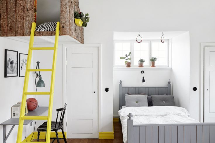 Stock image of a bedroom with a gray bed and yellow ladder going up to a raised loft area.