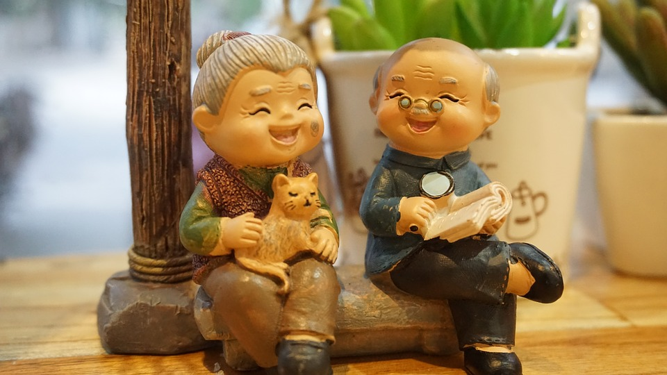 a figurine of an senior asian man and woman sitting laughing with a cat and book, happy in retirement from investing in Cash Offer Canada