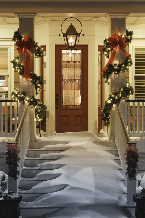 inviting christmas doorway with snow on porch stairs and railing