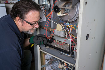 A man holding a flashlight while inspecting inside of a home furnace