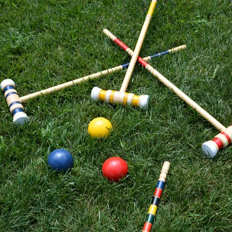 high angle view of multi colored croquet balls and mallets on grass lawn