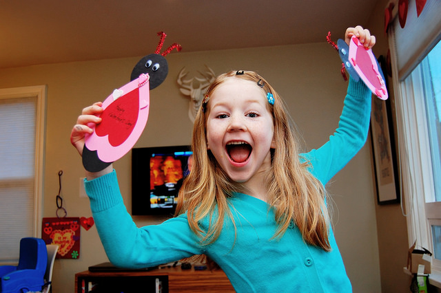 girl holding 2 homemade valentines